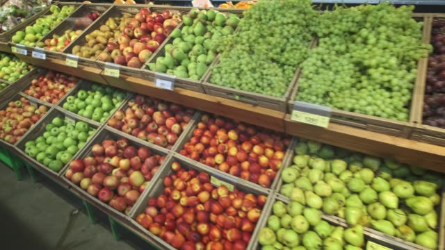 Many different fruits in the store on the shelves. Camera spans along racks.