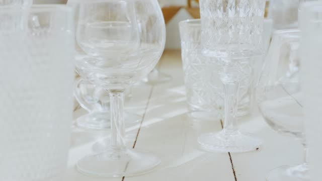 many different transparent glasses on the white wooben table, side view many different transparent glasses on the white wooben table, side view, handheld camera, 4k stock footage table top view stock videos & royalty-free footage
