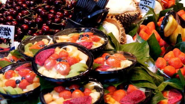 Muchos diferentes frutas tropicales en el mostrador del mercado. La gente elige frutas en Bazar o mercado de frutas, Barcelona, España - vídeo