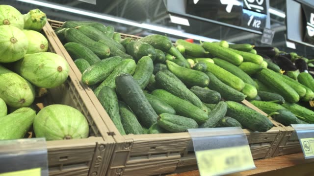Many different vegetables on the shelves in the supermarket. Cucumbers, cabbage, radishes, tomatoes.
