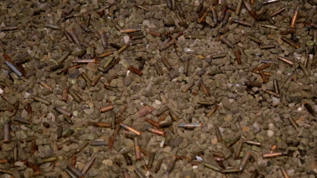 Many empty spent cartridges in a dash on stones. video