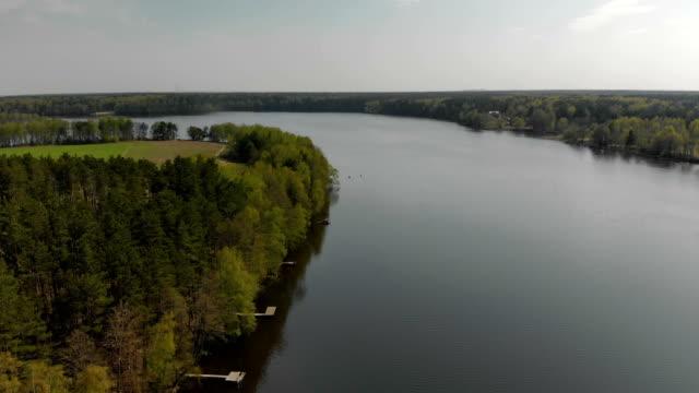 molti ponti di pesca lungo la pittoresca riva del bacino, il fiume con conifere - acqua dolce video stock e b–roll