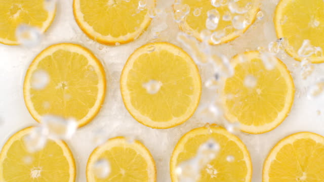 Many fresh lemon, top view of water flowing on a white background