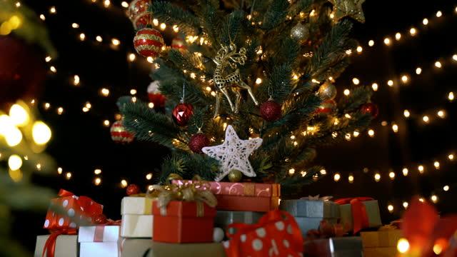 wiele pudełek na prezenty i ozdób świątecznych pod piękną zdobioną choinką z bokeh światłami w salonie w nocy - jodła filmów i materiałów b-roll