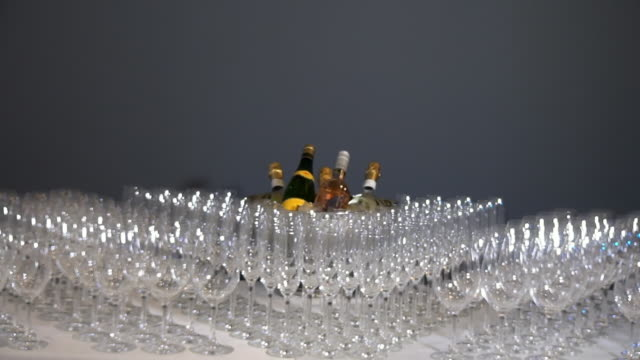 vídeos de stock e filmes b-roll de many glass goblets shine on banquet table on background of gray wall. - sideboard