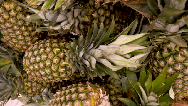 Many green pineapples closeup rotating on a 4K background in store for buyer.