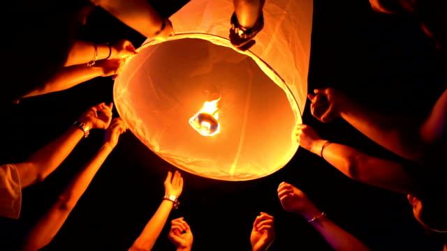 slo mo many hands floating sky lantern loi krathong and yi peng traditional festival, chiang mai province, thailand - китайский фонарь стоковые видео и кадры b-roll