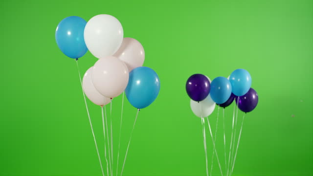 many helium balloons rise up on green screen. shot on red epic cinema camera. - przemieszczać się filmów i materiałów b-roll