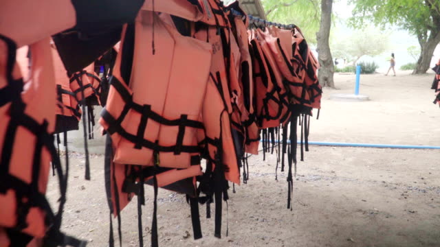 many Life vests on clothes line are only orange color. video