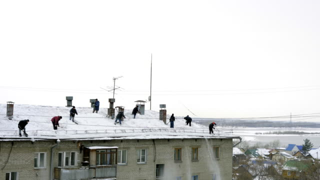 många män kastar vit snö från taket på en flervåningshus. - skyffel bildbanksvideor och videomaterial från bakom kulisserna