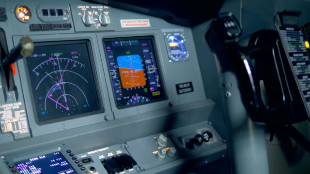 Many monitors on a plane dashboard, close up.