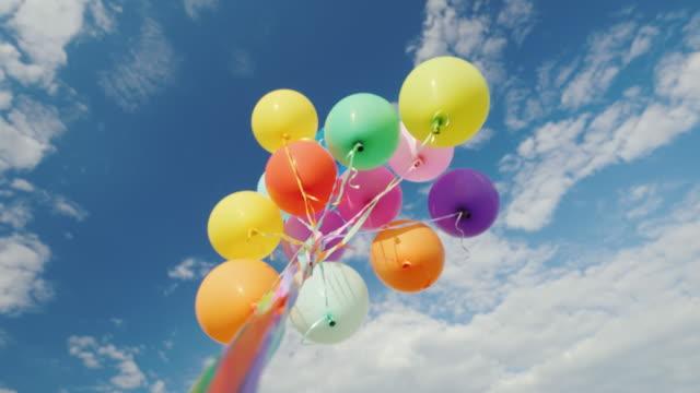 vídeos de stock, filmes e b-roll de muitos balões multicoloridos aspiram para o céu - punhado