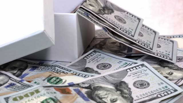 Many of 100 USA Dollars Bank notes in Gift Box Isolated on a White Rotating Table.