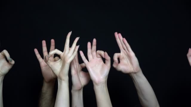 Many of hands showing ok sign on a black background. Close-up