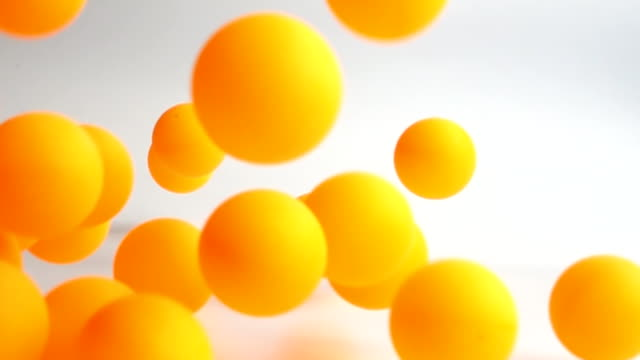 many orange balls falling in slow motion many orange balls falling and bouncing over the white surface slow motion yellow stock videos & royalty-free footage