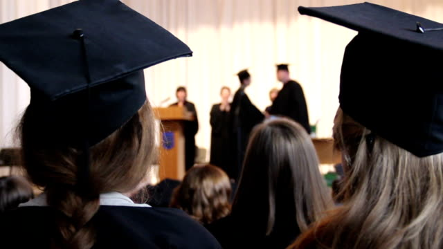 Many people at ceremony to celebrate graduation. Dean shaking video