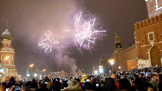 many people gathered for a universal celebration new year's in moscow. fireworks on red square near the spasskaya tower on new year's eve. multicolored salute in the kremlin. - nazionalità russa video stock e b–roll