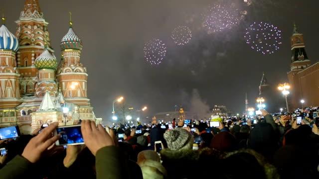 många människor samlades för en universell fest nyår i moskva. fyrverkerier på röda torget nära spasskaya tornet på nyårsafton. mångfärgad honnör i kreml. - röda torget bildbanksvideor och videomaterial från bakom kulisserna