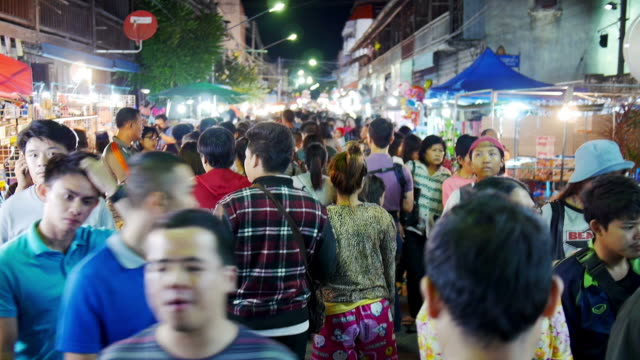 many people making their way through at night market in thailand - ночной рынок стоковые видео и кадры b-roll