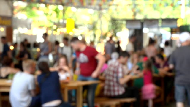 Many people sit at the tables and eat at the festival video