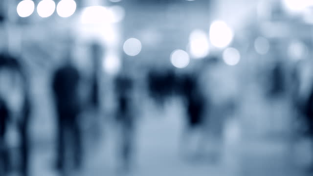 Many people walk inside the mall exhibition store. Blurred Background