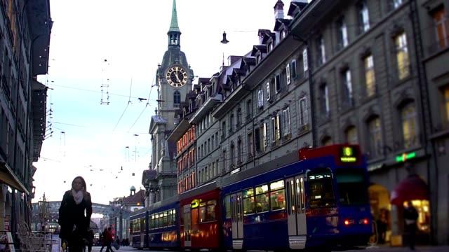 viele menschen gehen und öffentliche verkehrsmittel fahren entlang der antiken europäischen street - kanton bern stock-videos und b-roll-filmmaterial
