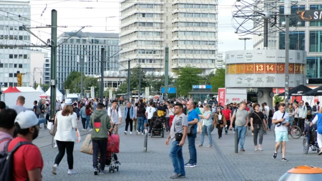 Many People walking on crowded street or busy city square (Alexanderplatz) in Berlin
