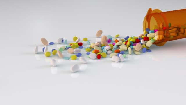 vídeos y material grabado en eventos de stock de muchas píldoras que salen de la botella de píldora sin receta en fondo blanco aislado en cámara lenta - recipiente para las píldoras