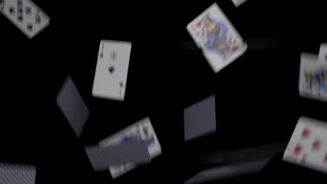 多くのトランプがスローモーションで黒い背景に落ちる ビデオ