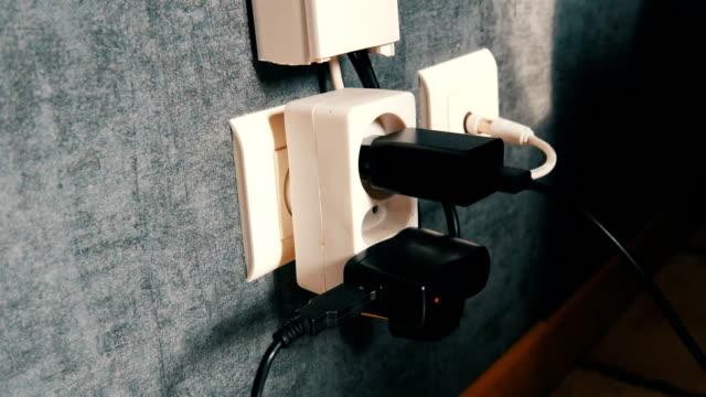 viele stecker in die steckdose. adapter-ladegerät in die steckdose - steckschlüssel stock-videos und b-roll-filmmaterial