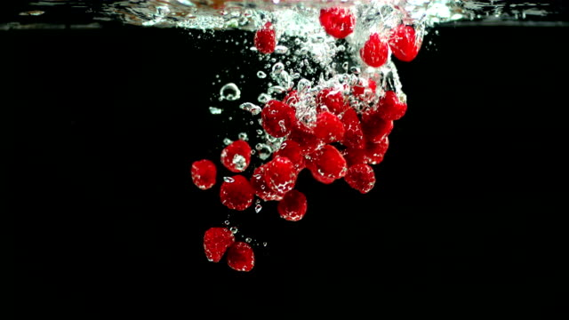 vidéos et rushes de beaucoup de framboises tombant dans l'eau - baie eau
