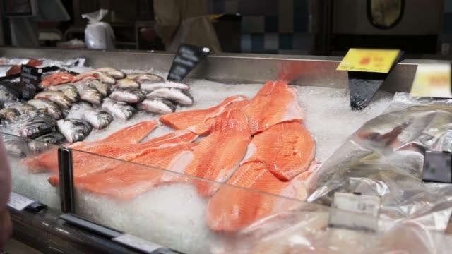 vídeos de stock, filmes e b-roll de muitos peixes crus em cama de gelo esmagado no mercado de peixes. grupo de diferentes peixes, dorada e salmão no gelo. - frutos do mar