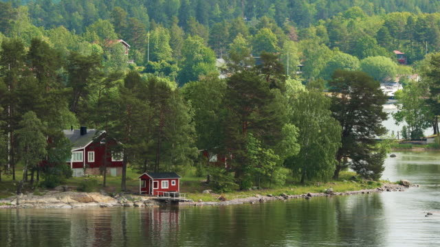 många röda svenska trä bastu timmerstugor hus på ön kusten på sommaren molnigt dag - summer sweden bildbanksvideor och videomaterial från bakom kulisserna