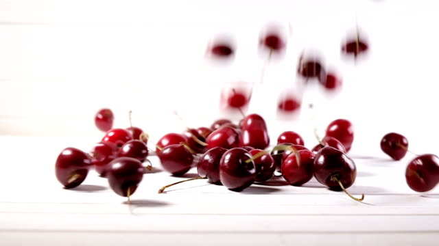 Many ripe cherries are falling down on a white background, slow motion
