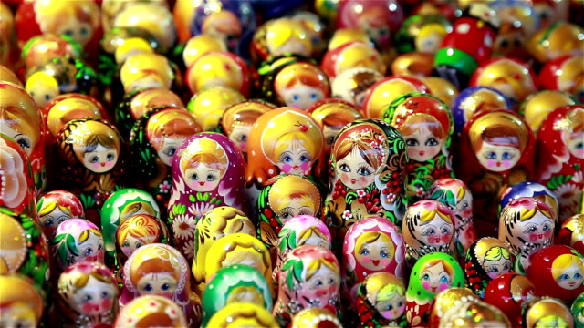 Many Russian wooden souvenirs (matrioshka, nesting dolls) on the counter. video