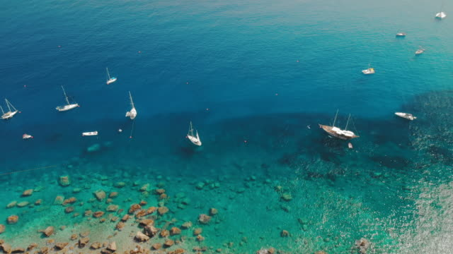 taormina, sicily, italy - august 2019: many sailing boats and luxury yachts moored near the coast of the island. colorful water and sand. aerial drone shot - sicily filmów i materiałów b-roll