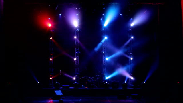 Many spotlights that illuminate the stage at a concert with fog.