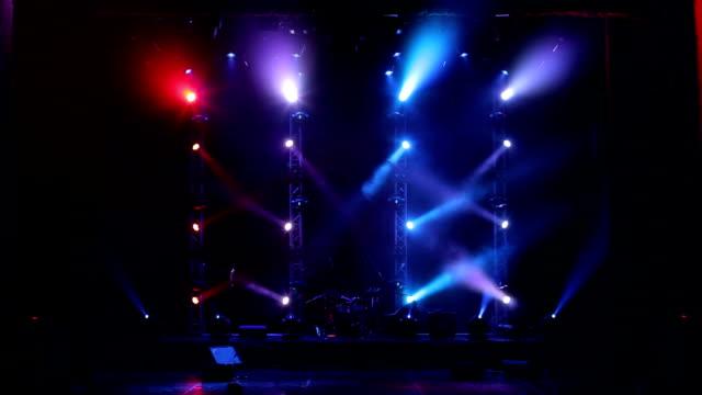 vidéos et rushes de plusieurs projecteurs qui illuminent la scène lors d'un concert avec brouillard. - art du spectacle