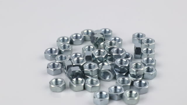 many stainless hex nuts rotating on a white background close-up, side view many stainless hex nuts rotating on a white background close-up, side view bolt fastener stock videos & royalty-free footage