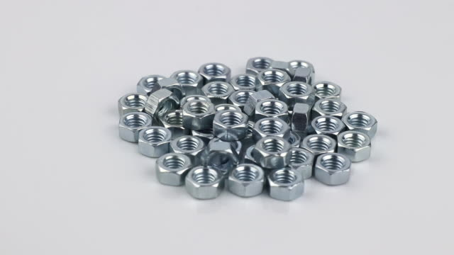 many stainless hex nuts rotating on a white background, side view many stainless hex nuts rotating on a white background, side view bolt fastener stock videos & royalty-free footage