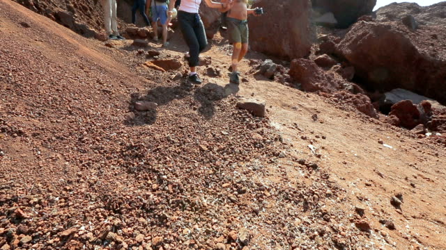 Many tourists walking along dangerous slope of volcanic origin mountains video