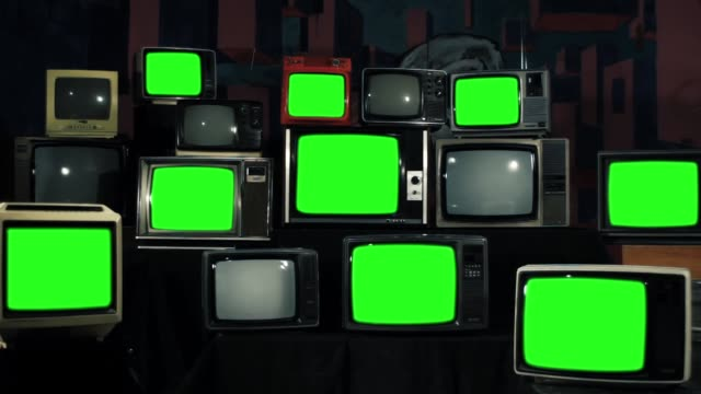 Many TVs with Green Screens. Zoom In. Green Screens Turning Off. Aesthetics of the 80s.