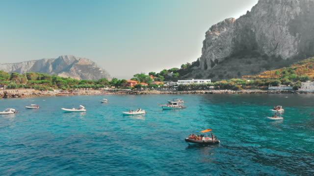 stockvideo's en b-roll-footage met palermo, sicilië, italië-augustus 2019: veel niet-herkende luxe jachten in de buurt van het rotsachtige strand van groene bomen. transparant turquoise water van de zee. luxe rust voor rijke mensen. niet-herkende toeristen genieten van zwemmen in de oceaa - cruise