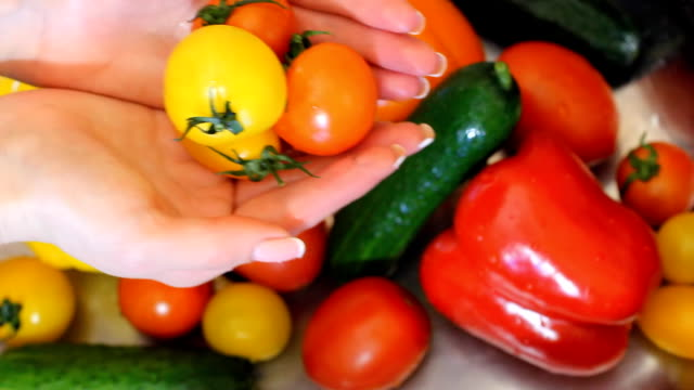 Many vegetables of various kinds lick in the sink and are ready for washing. Red and yellow tomatoes, green cucumber and yellow, red and orange peppers. Young girl housewife petting works on vegetable vabrike. Stretches into the frame of the hand with video