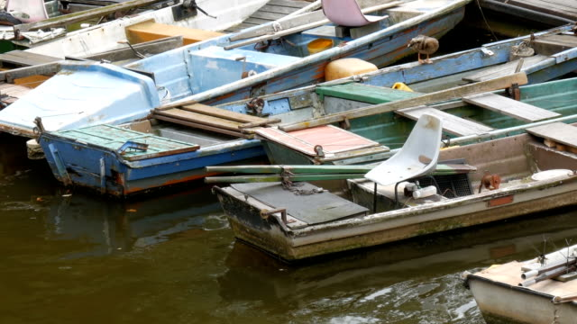 Many vintage old boats stand on the dock on river