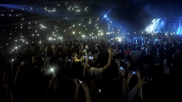 Many young people filming concert on smartphones. Addiction to gadgets video