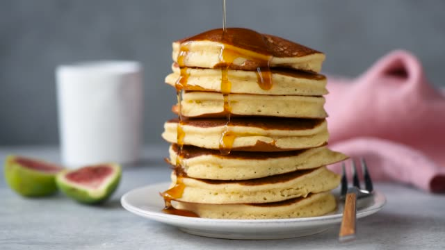 maple syrup pouring on stack of pancakes - сироп стоковые видео и кадры b-roll
