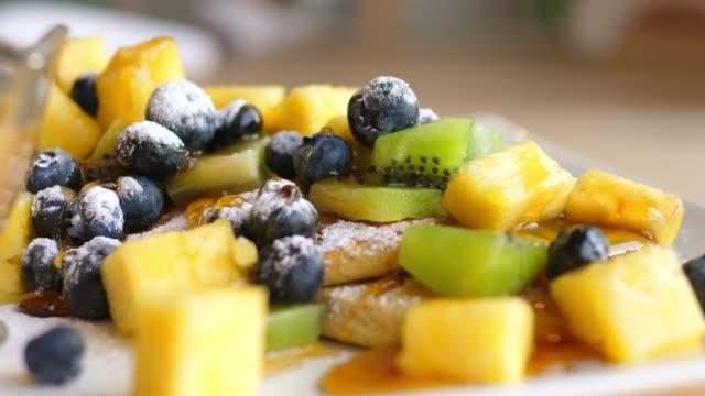 ahornsirup pouring ontonkuchen mit früchten und beeren. closeup - ahorn stock-videos und b-roll-filmmaterial