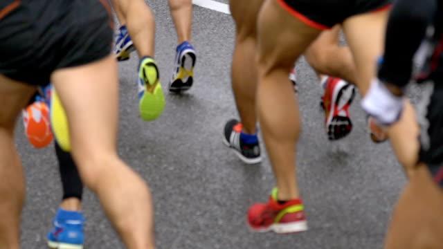 Piernas de los corredores de maratón en cámara lenta - vídeo