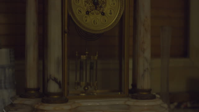 Marble clock with a black lion sculpture in a creepy haunted house on a winter night. Tilt up tight shot. Halloween scary ambiance. Ghost, Demon or Spirit. Shot on RED SCARLET 6K.